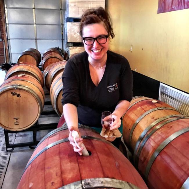 amanda of southern connecticut wine company topping off wine barrels